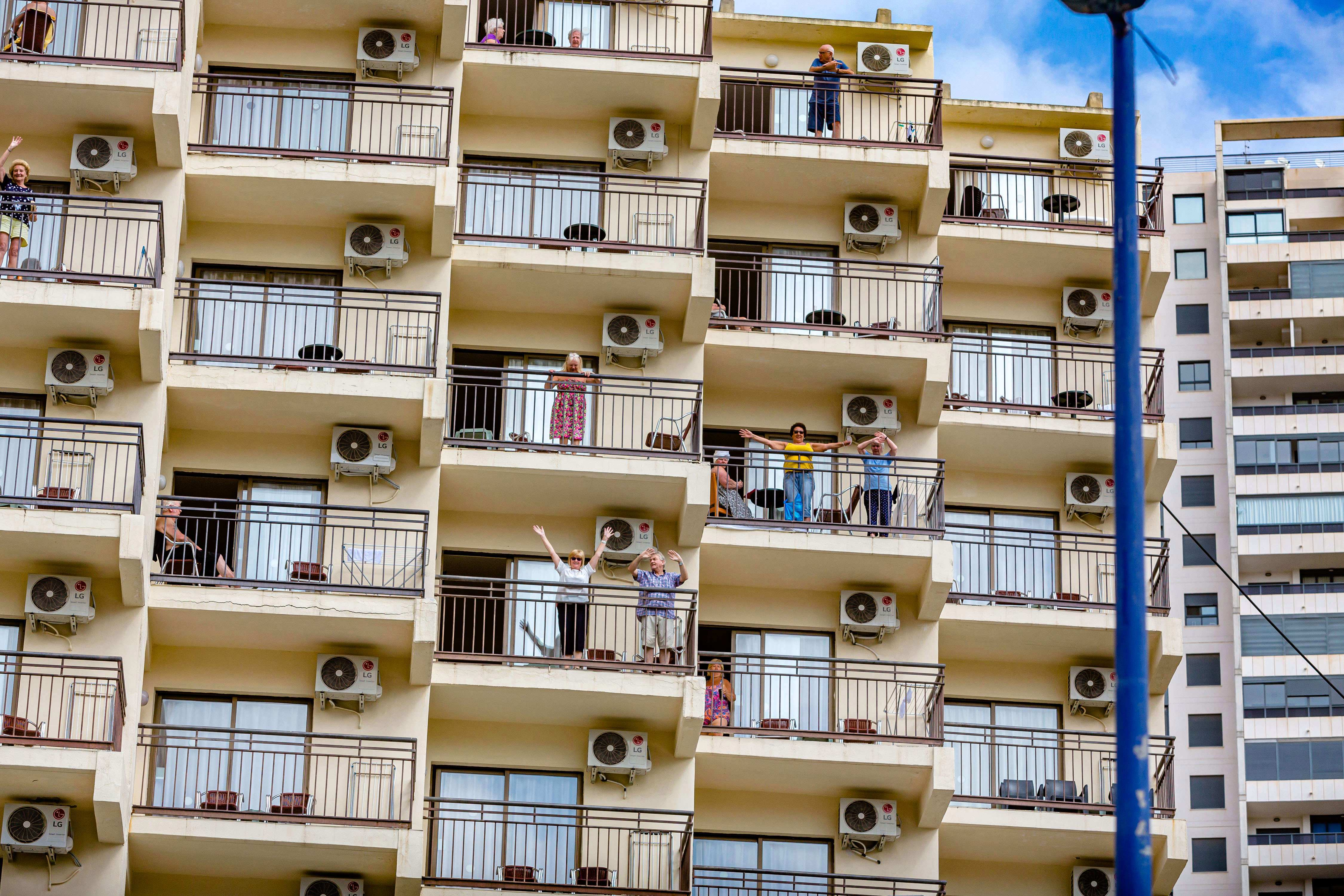Stranded Brits wave from their hotel balconies in Benidorm