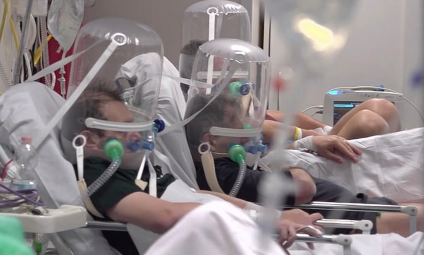 Patients in northern Italy wear bubble-like apparatus on their heads to help with their breathing