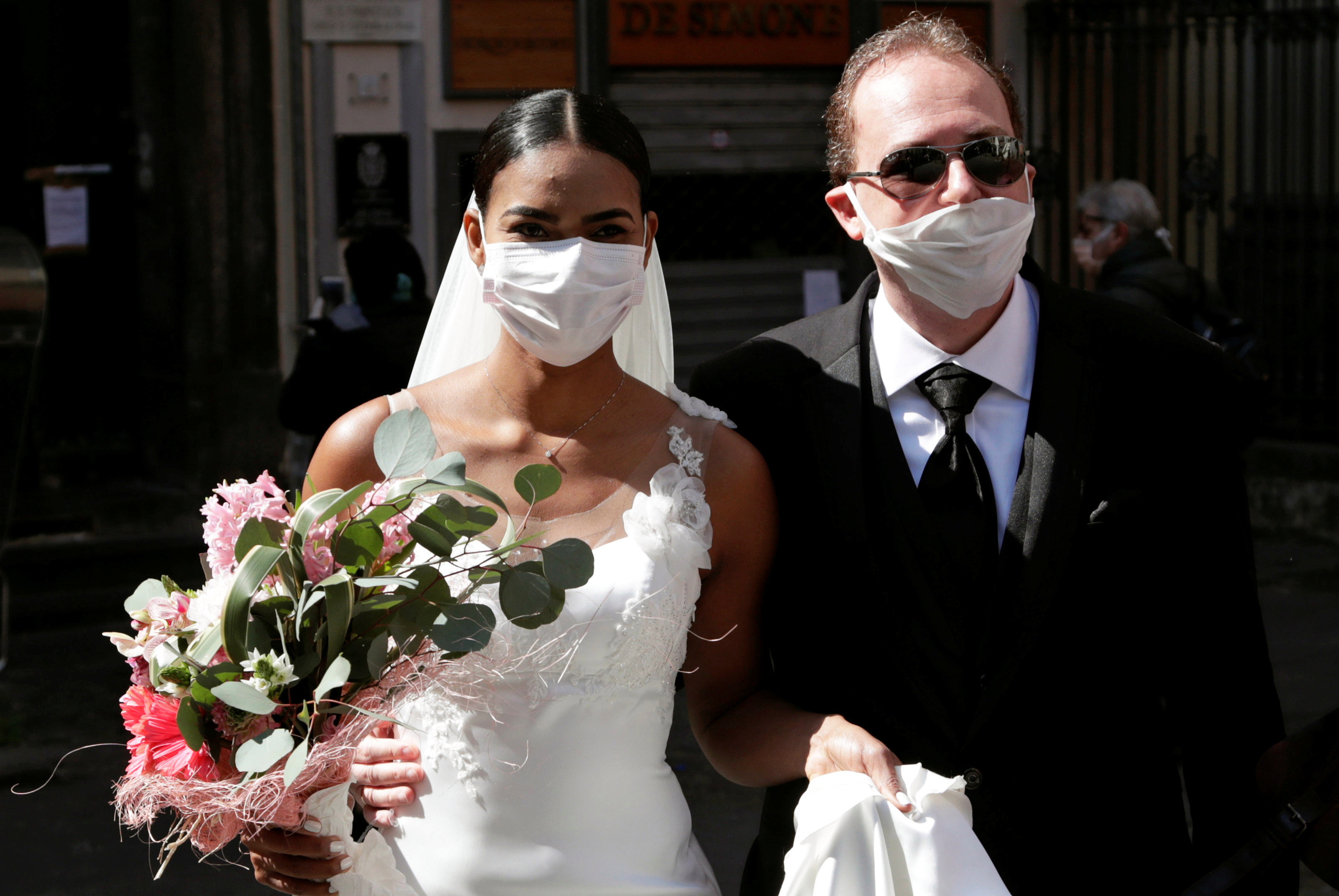 The pair donned face masks for their unconventional wedding snaps