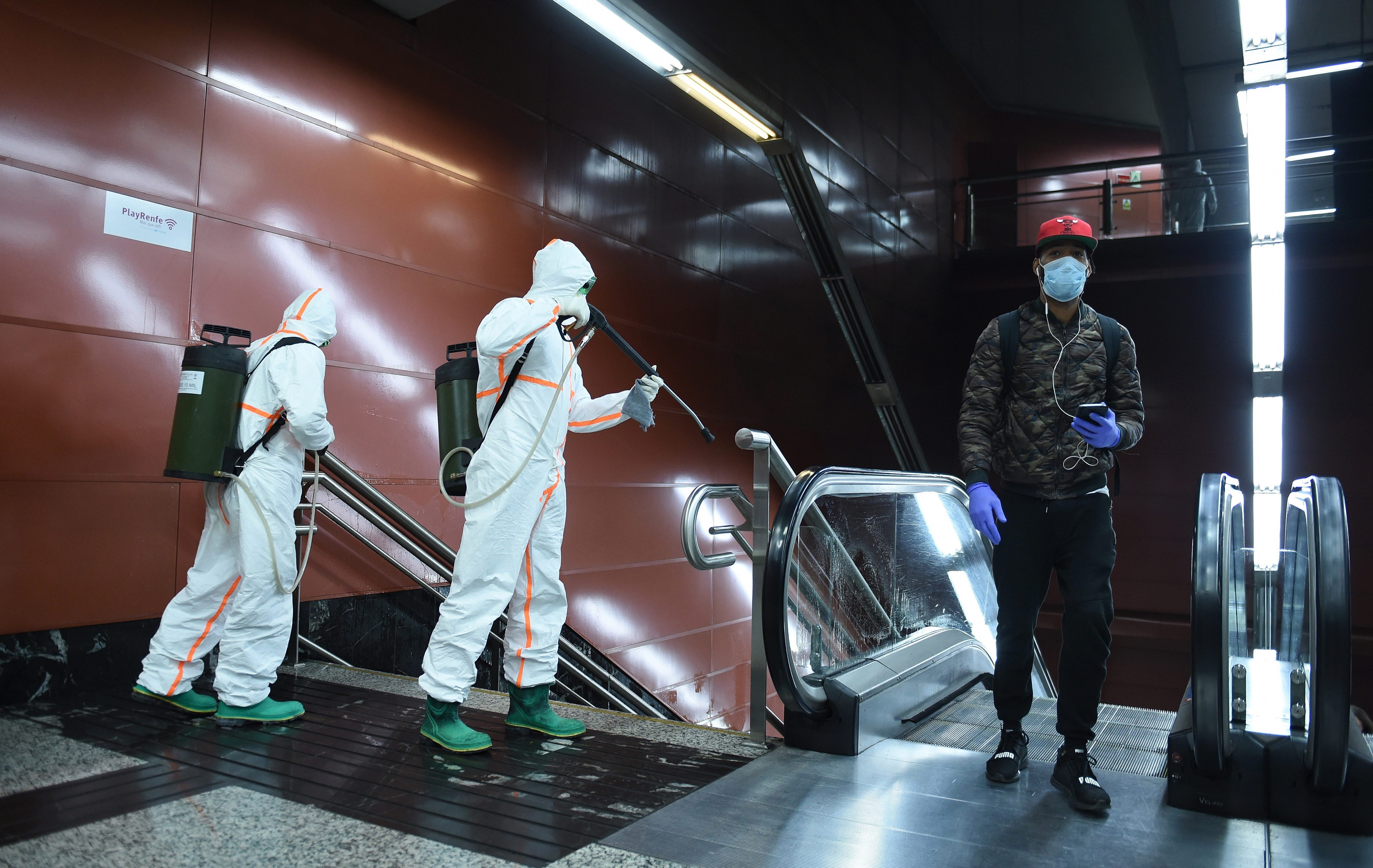 Workers are seen disinfecting a public escalator in Madrid, Spain