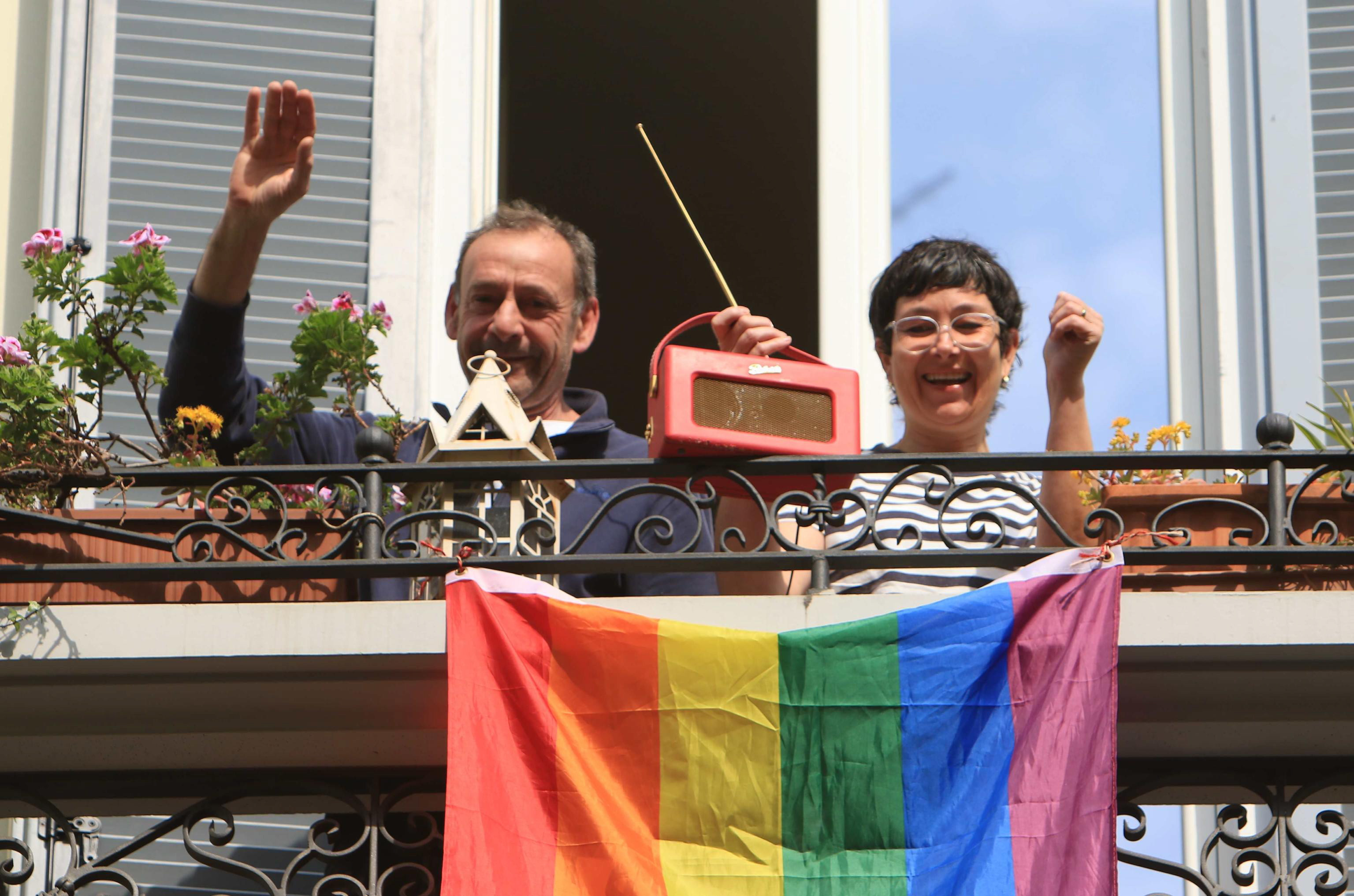 A Spanish couple under quarantine wave from their balcony