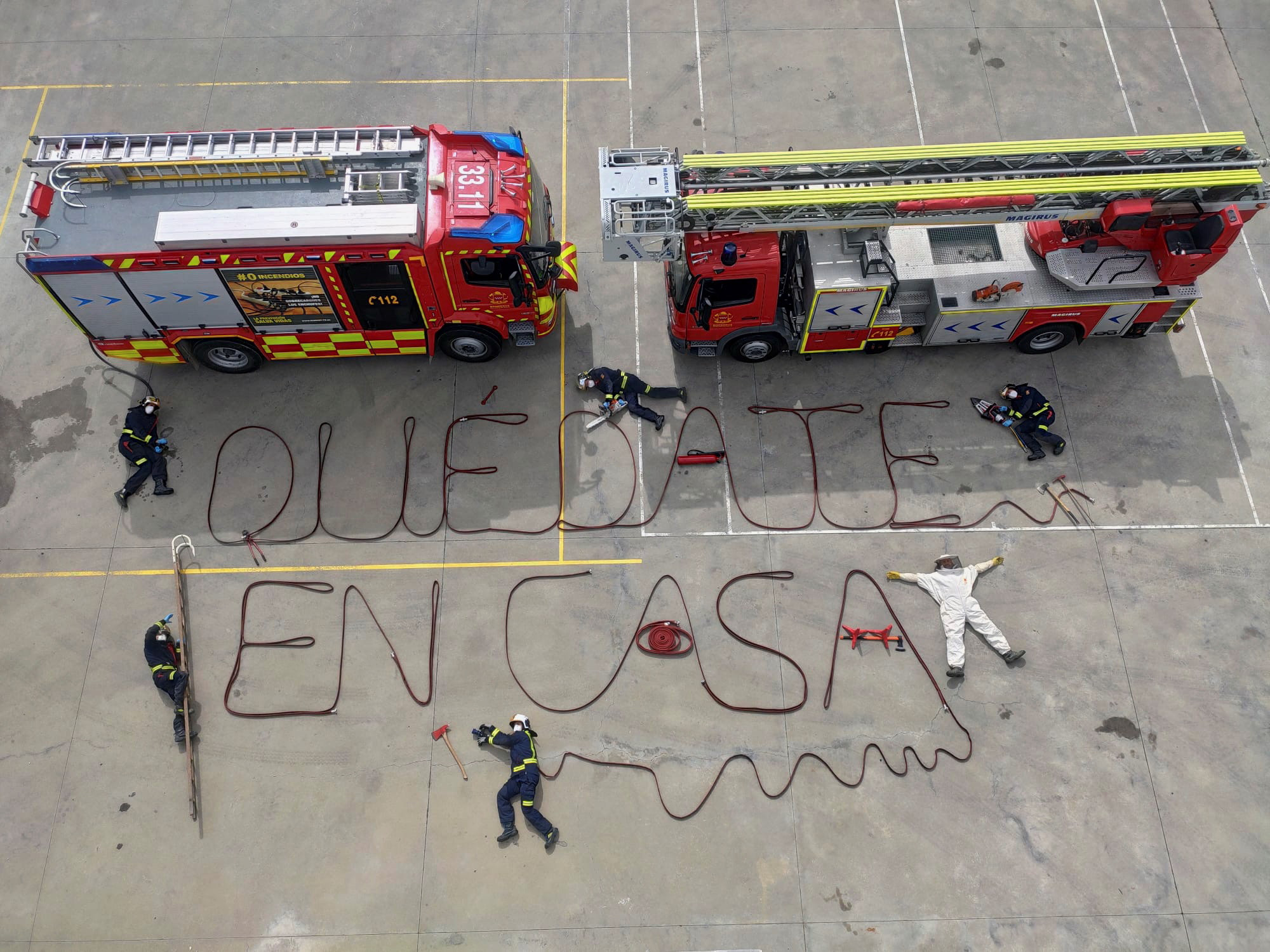 Firefighters write the sentence 'Stay at Home' in Spanish