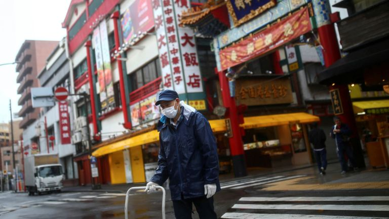A worker, wearing protective face mask following an outbreak of the coronavirus disease (COVID-19), is pictured on an almost empty street in Yokohama?s Chinatown, south of Tokyo, Japan March 10, 2020. REUTERS/Edgard Garrido