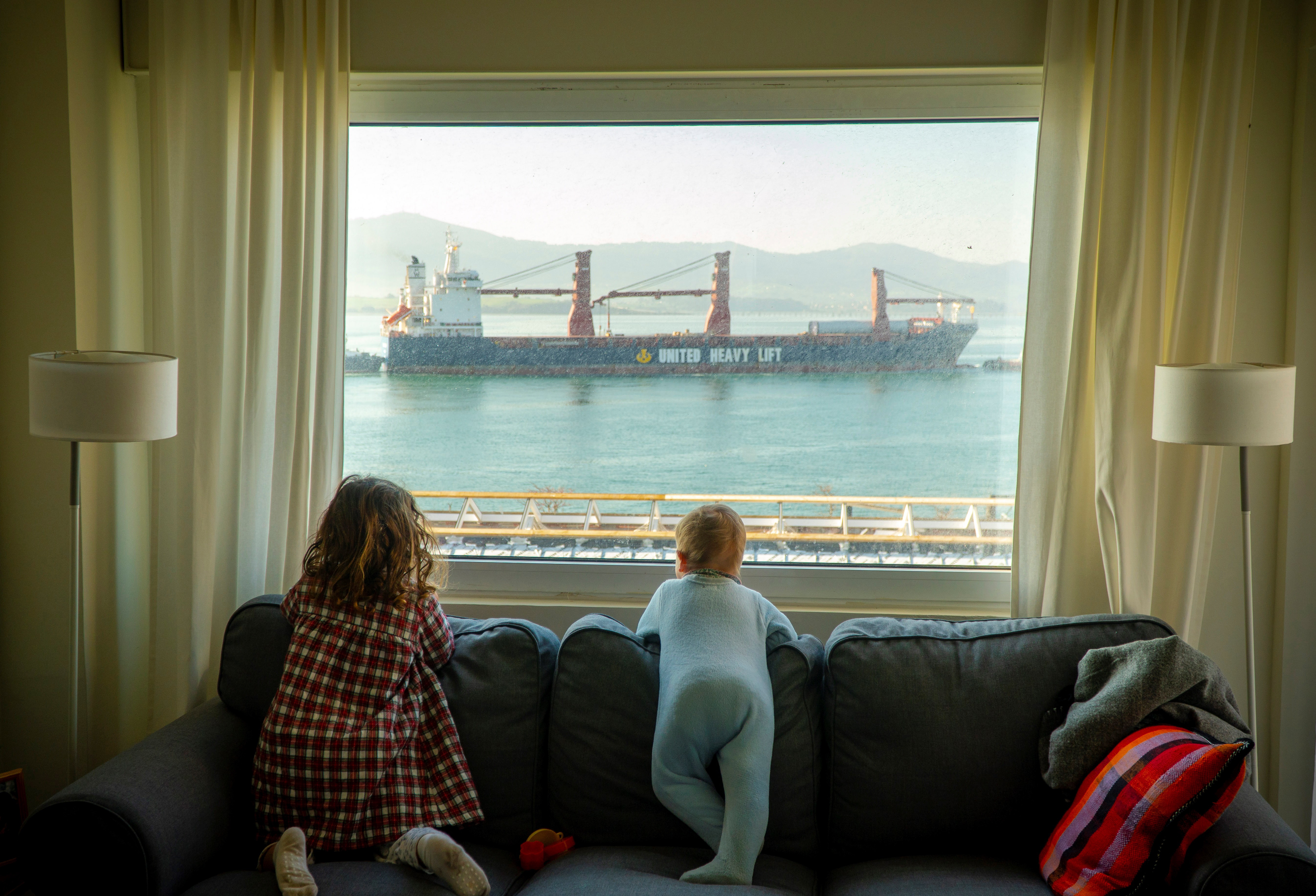 wo young girls look at the merchant ships docking at the port from the window of their house, during the coronavirus emergency lockdown, in Santander, Spain