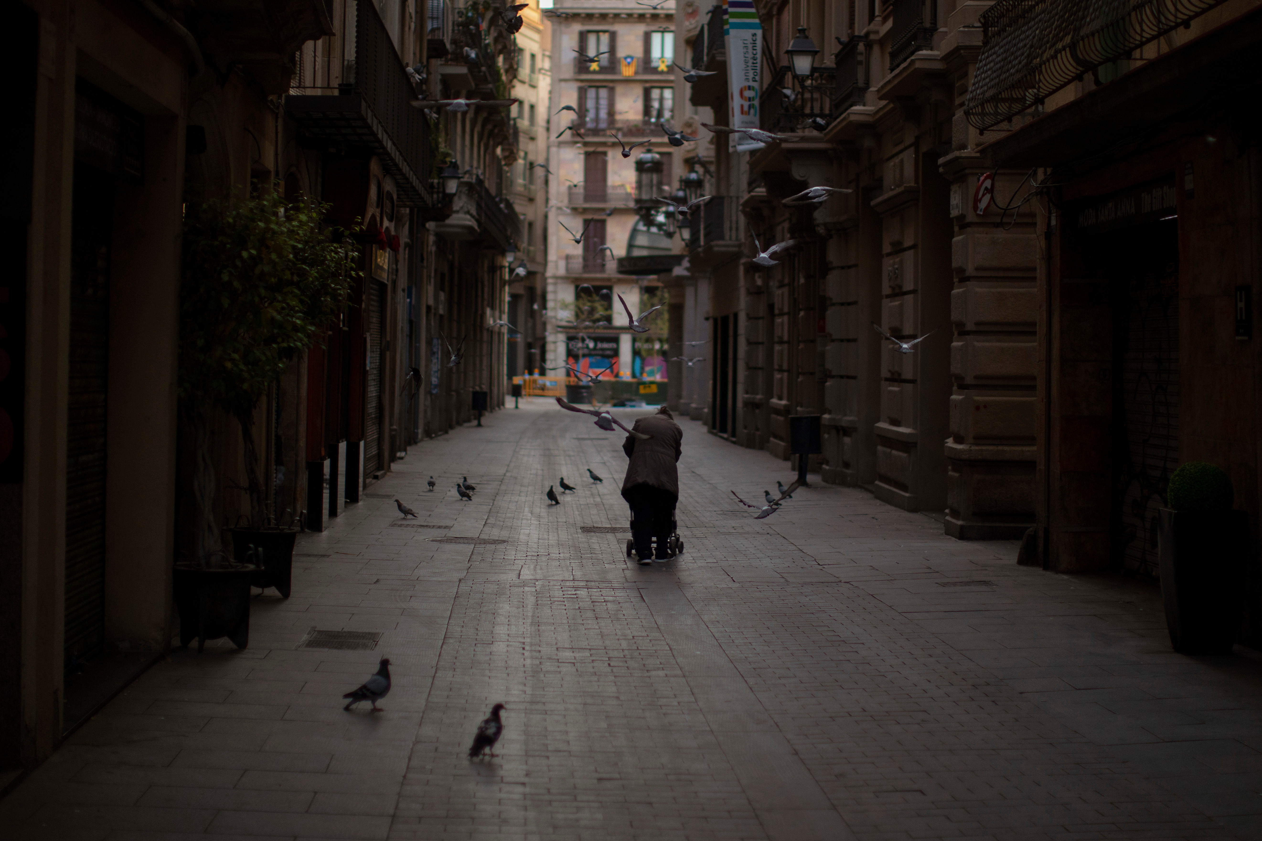 A woman pushes a cart with her belongings as she walks along the once bustling streets of Barcelona