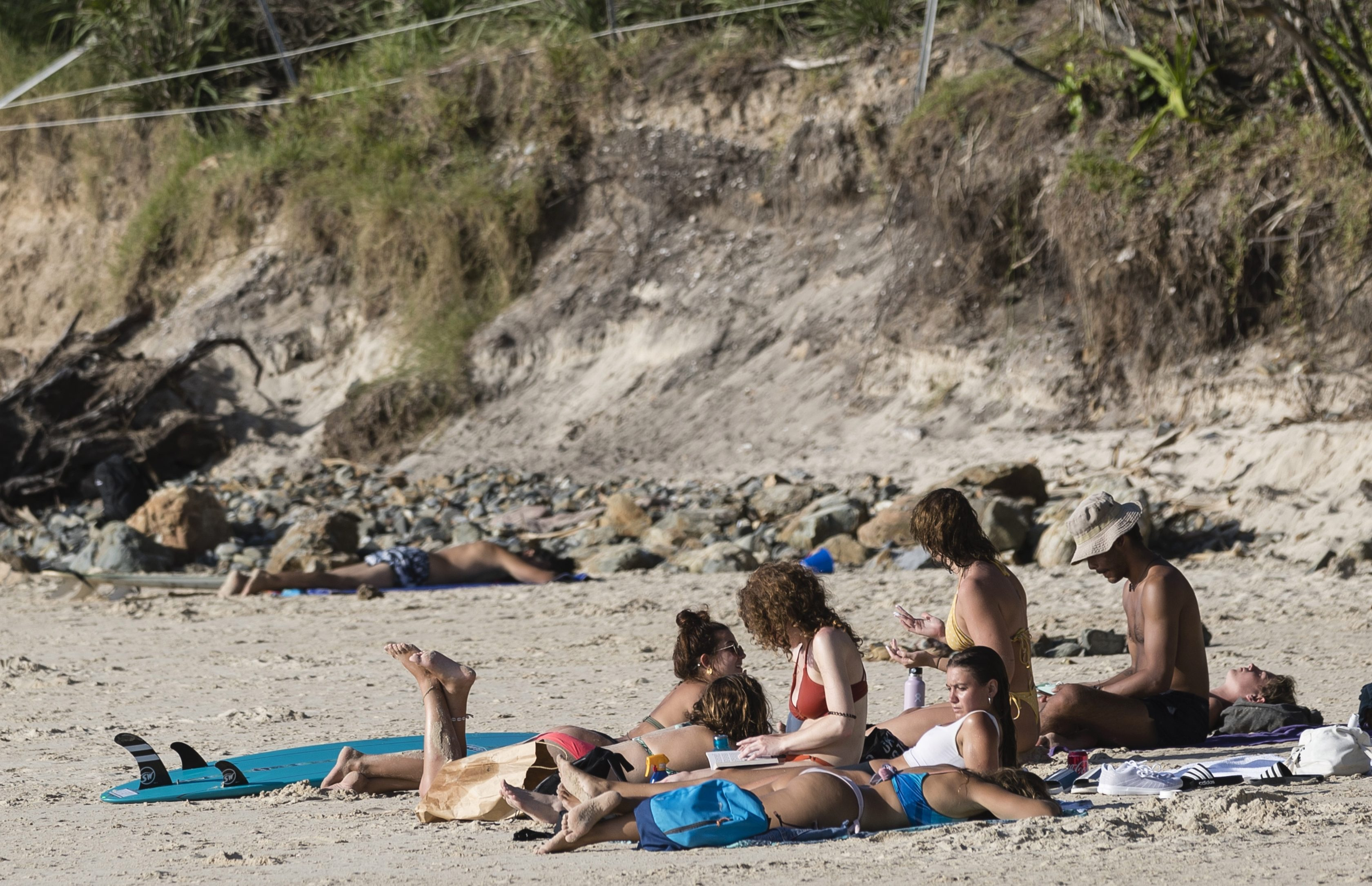People gather at the beach known as The Pass before the lockdown