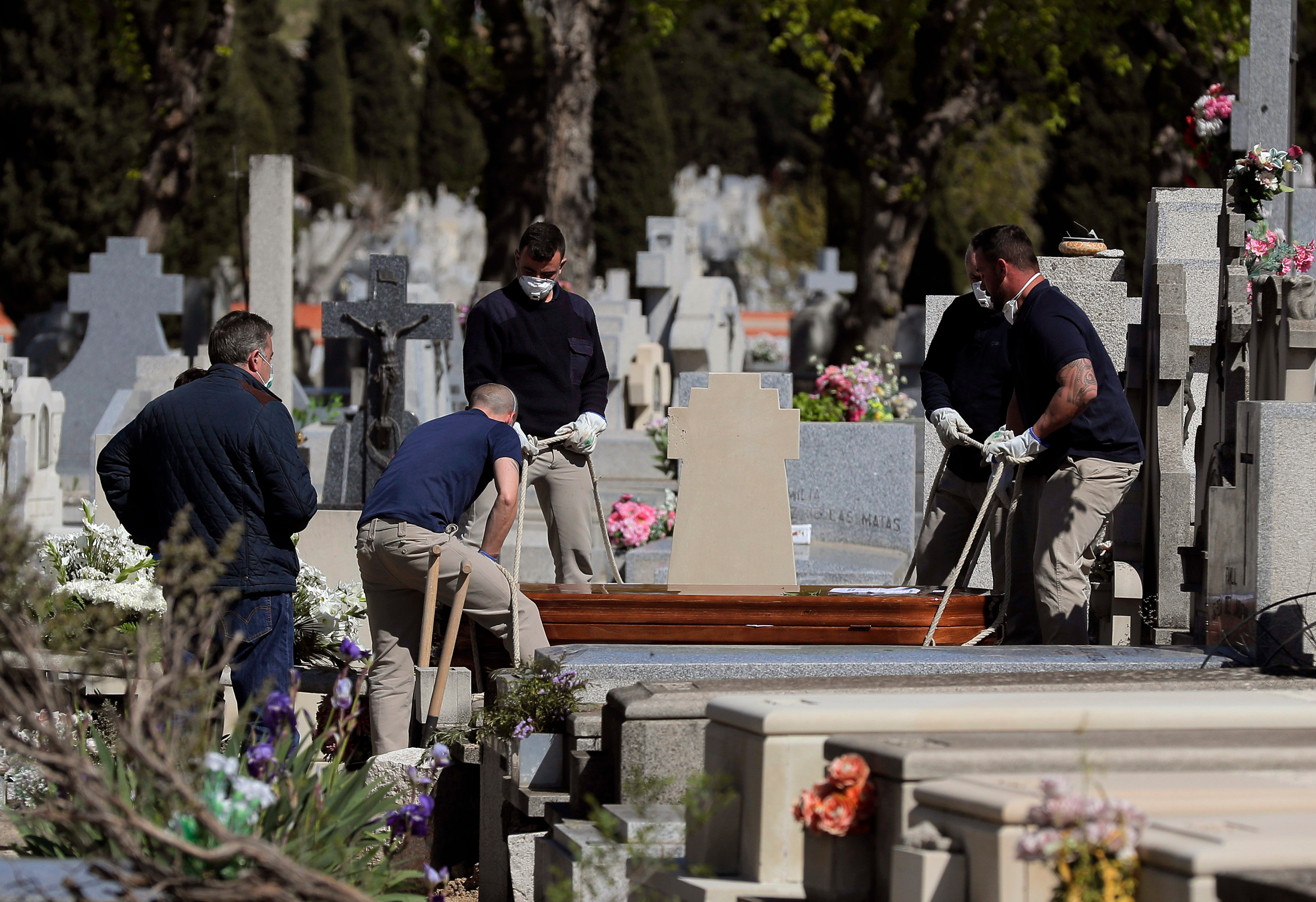 Pallbearers carry a coffin of a person who died of COVID-19 at the cemetery of La Almudena in Madrid