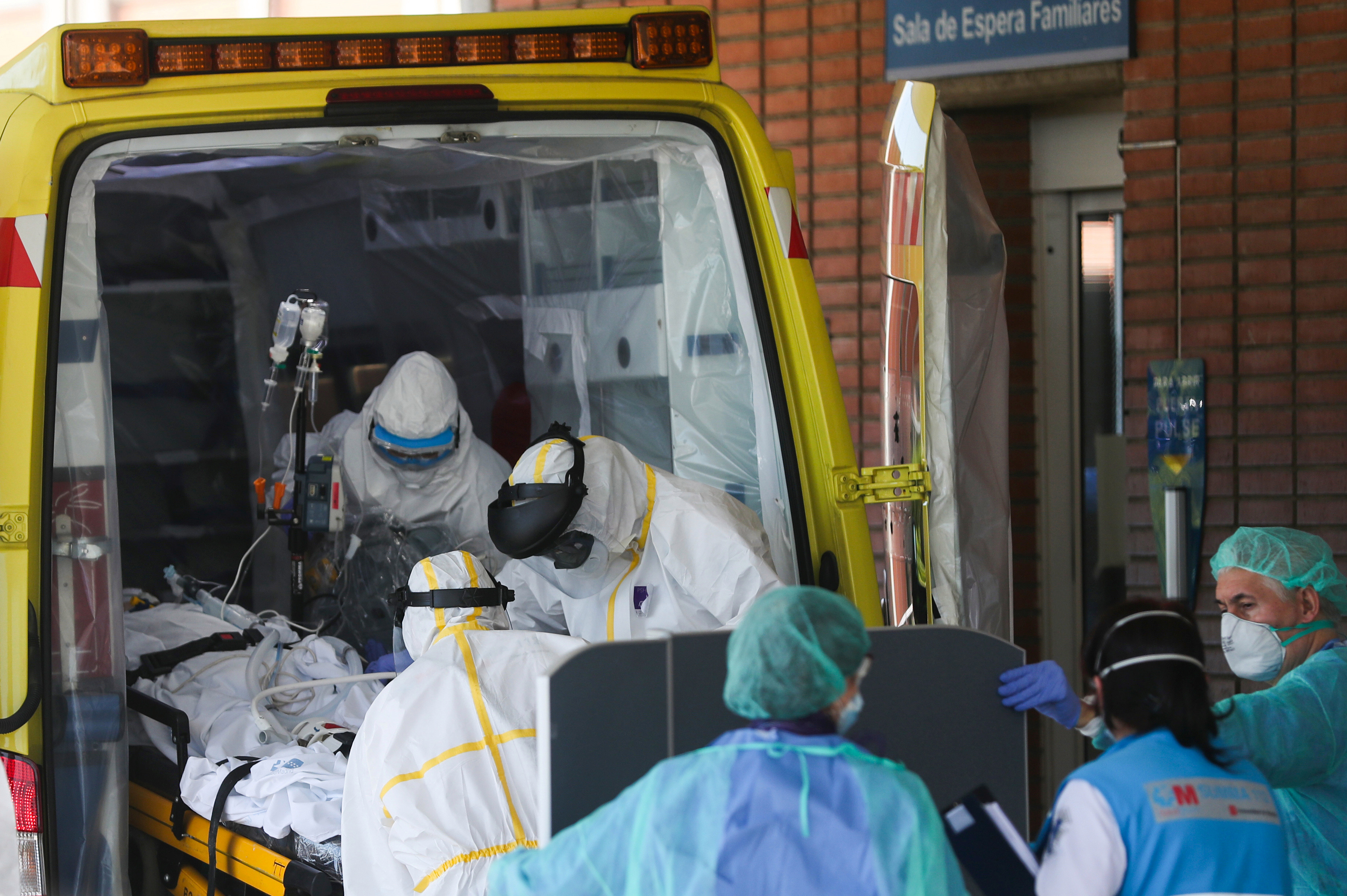 Paramedics wearing hazmat suits help a patient into a hospital in Spain