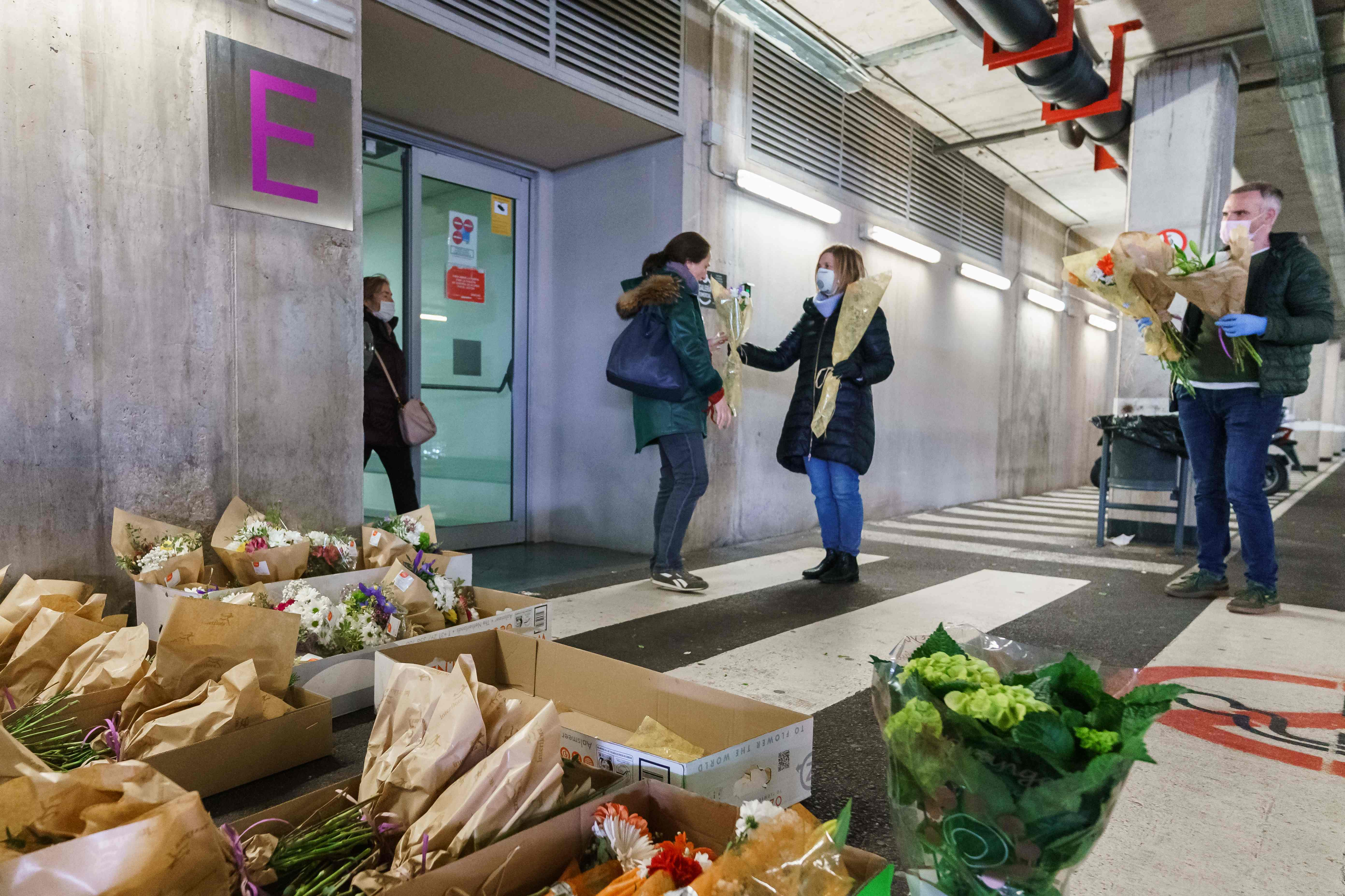 A florist hands a bouquet of flowers to a health worker outside the Burgos Hospital in Burgos, in northern Spain