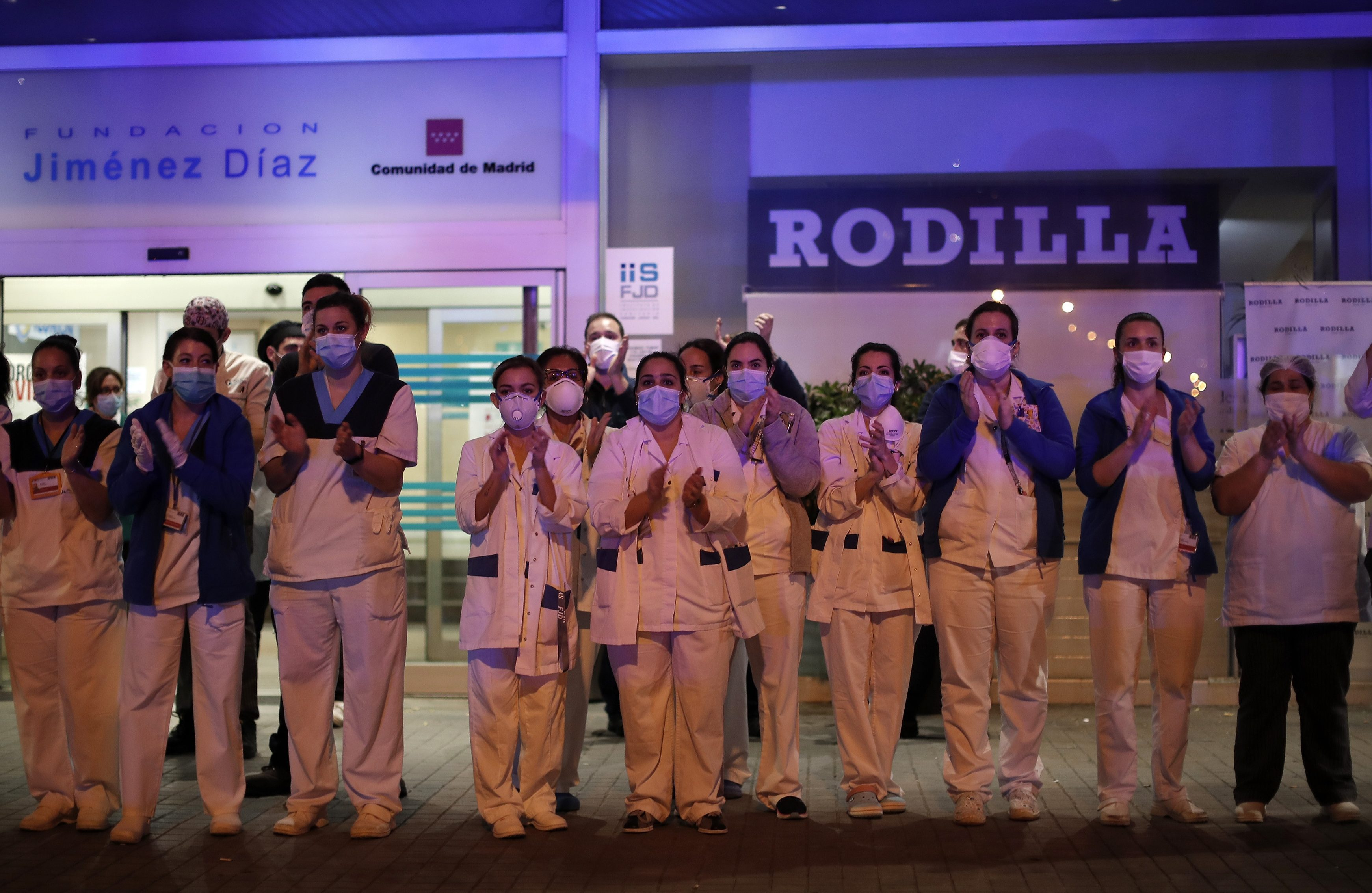 Health officials applaud Spanish police outside a hospital in Madrid