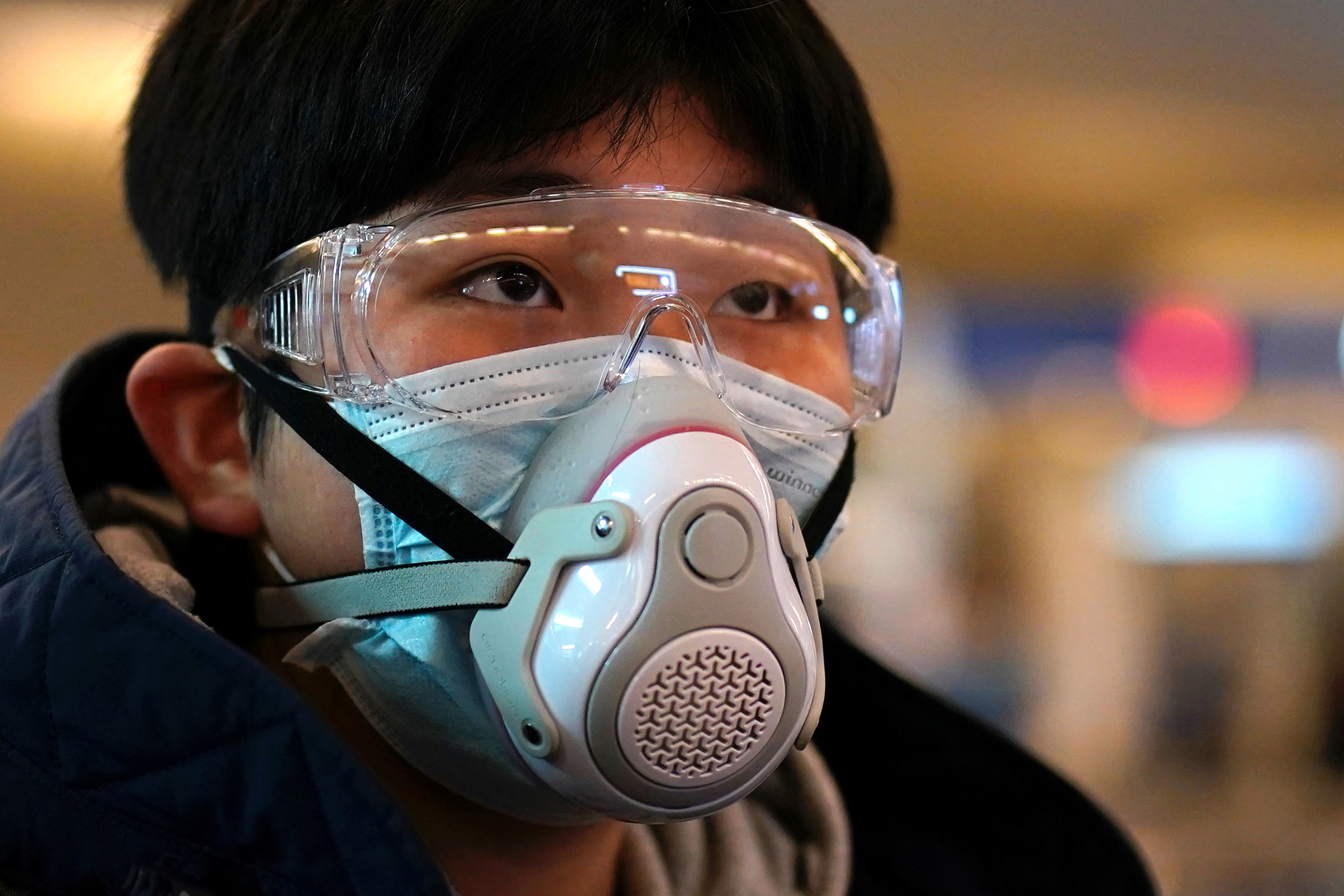 A passenger wearing a protective mask arrives at a railway station in Wuhan on the first day inbound train services resumed