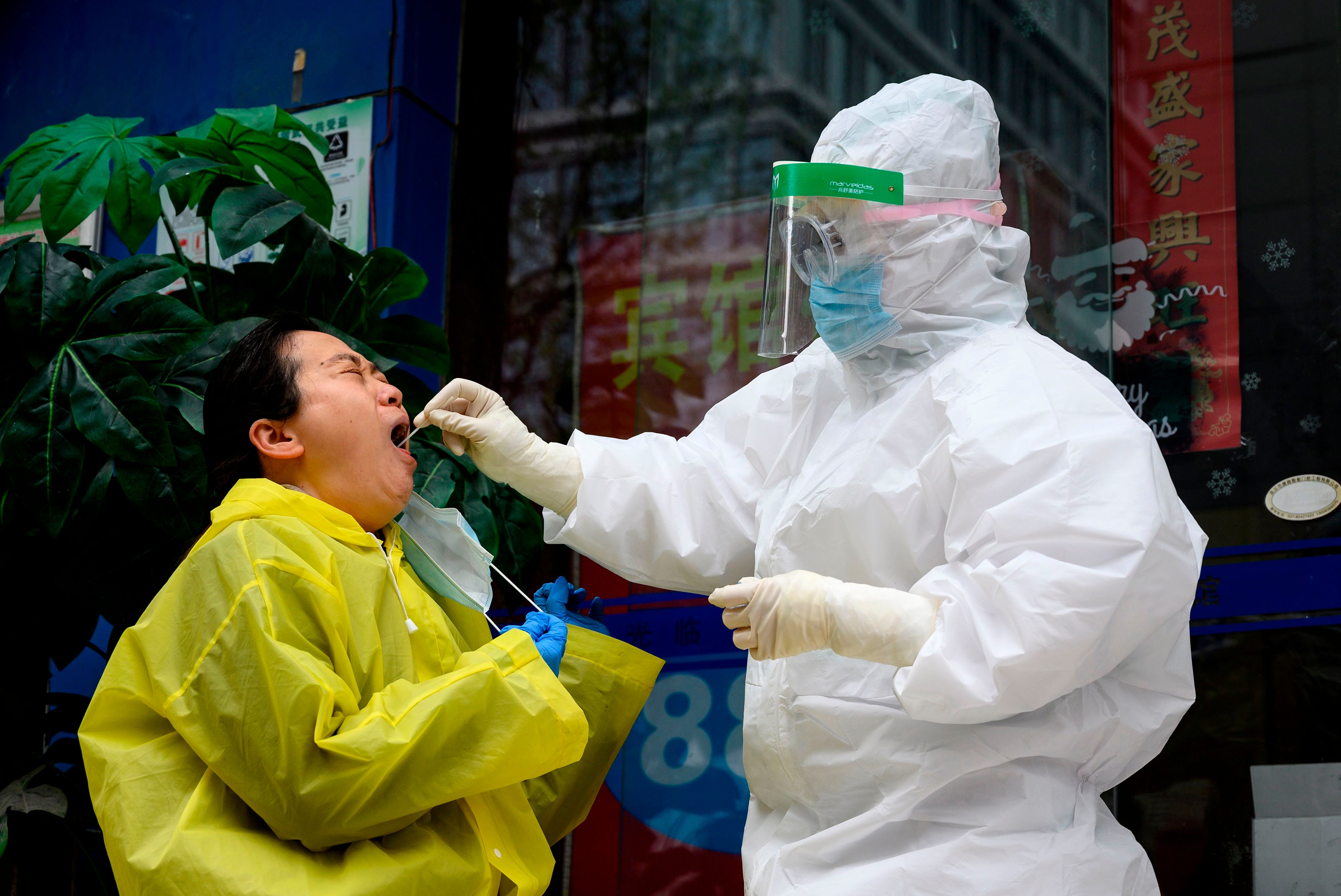 A medical worker wearing a hazmat suit swabs a woman to check if she has coronavirus in Wuhan, China's central Hubei province on March 28