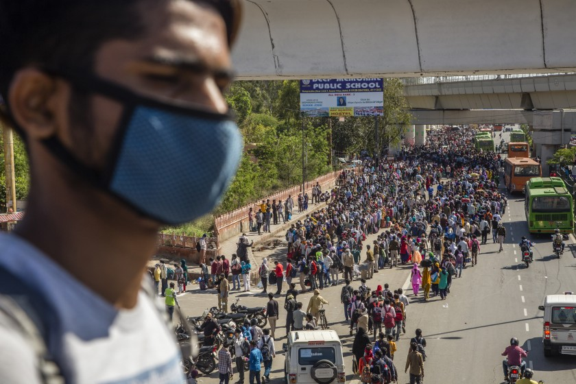 Crowds of Indian migrant workers wait to board buses to return to their native villages amid a nationwide lockdown on March 28 in Ghaziabad, outside New Delhi.