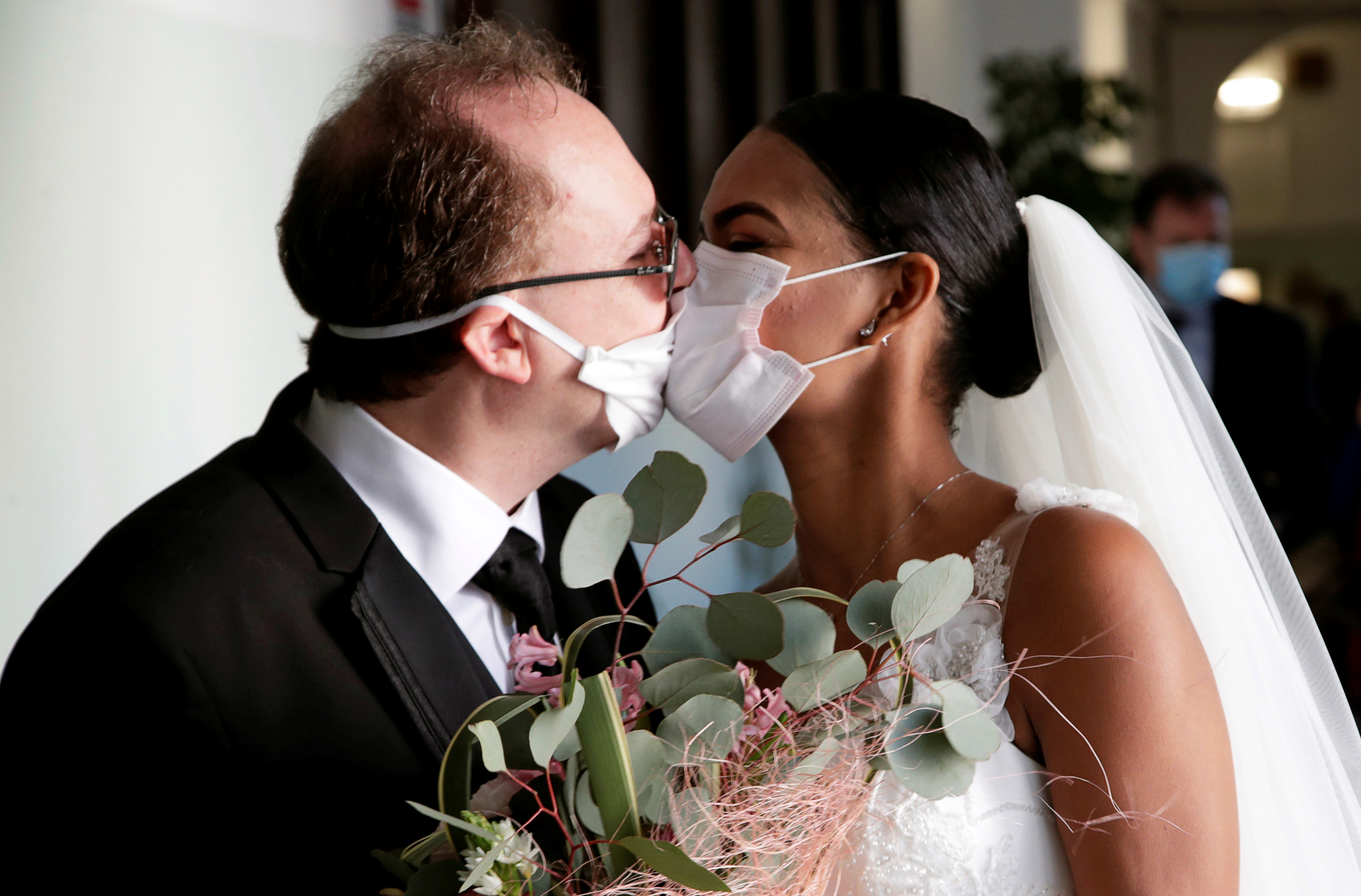 The pair kiss through protective face masks