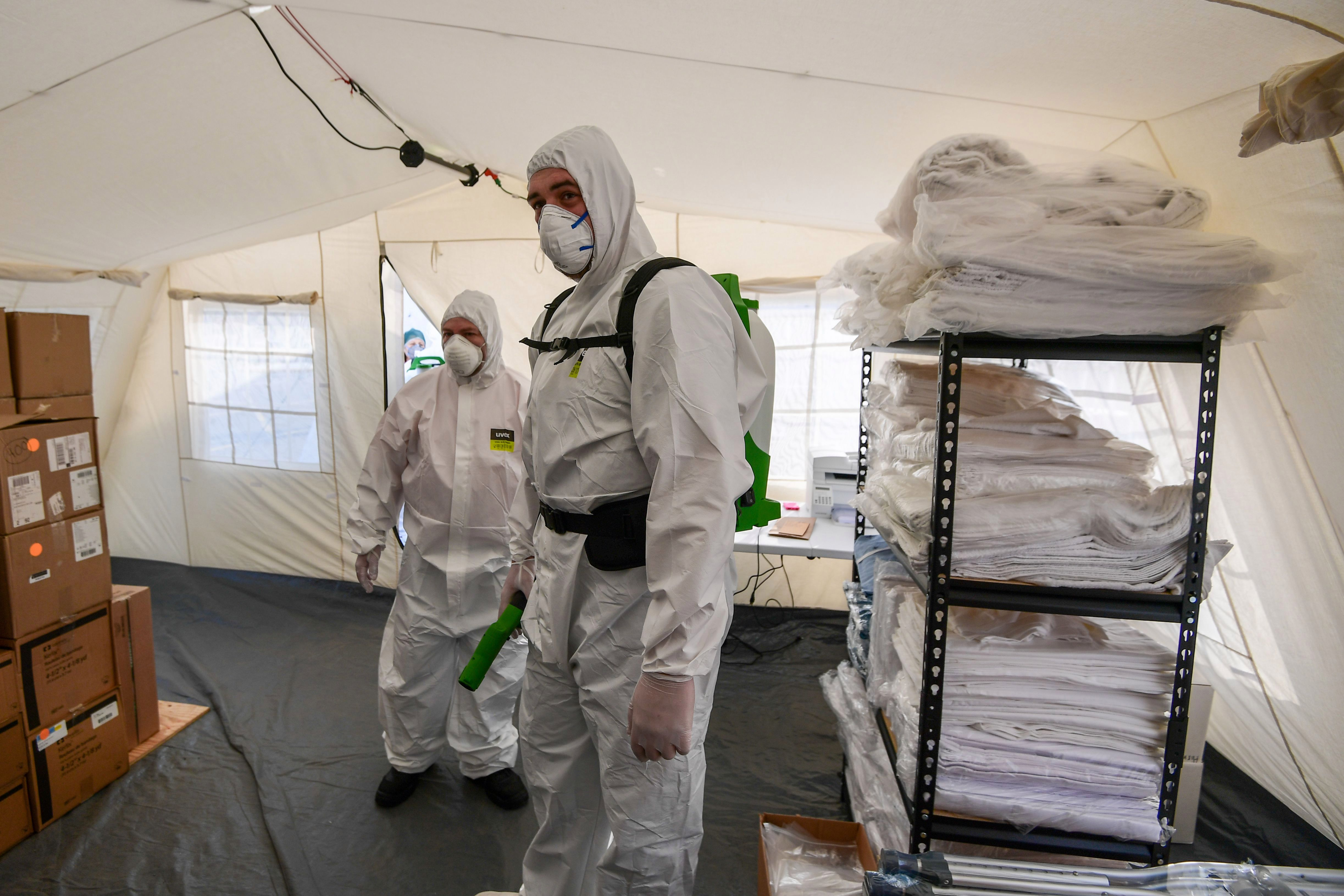 Cleaning staff from a newly operative field hospital in Cremona, near Milan. Italy is now the new epicentre of the outbreak
